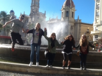 TEFL Students jumping for joy in front of a fountain.